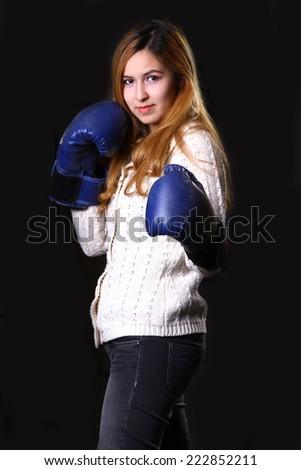 Funny girl female boxer model wearing big fun pink gloves playing sports boxing studio shot black background  - stock photo