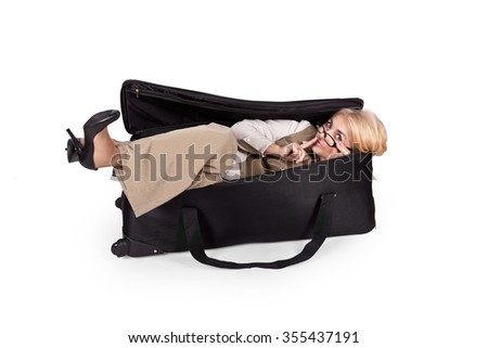 Funny girl in a business suit hides in a big bag shows sign of silence
