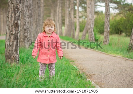 funny girl in a pink coat standing in the park