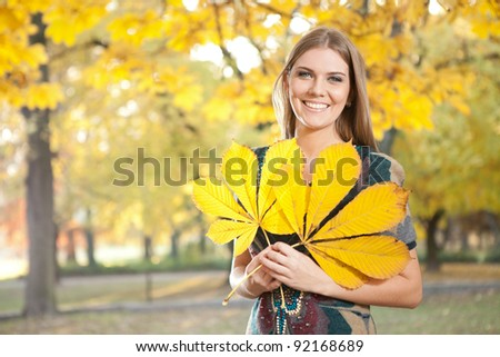 funny girl in autumn park holding leaves - stock photo
