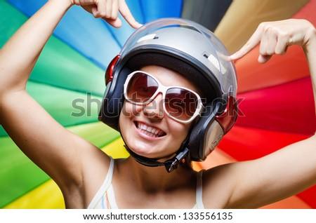 Funny girl in helmet having fun. Multicolored background. - stock photo