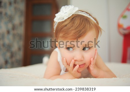 funny girl lying in bed and showing tongue  - stock photo