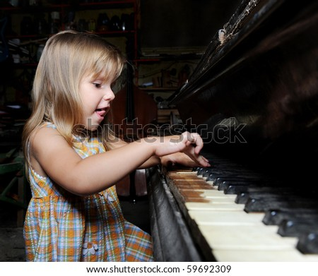Funny girl playing on an old black piano