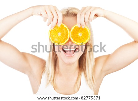 Funny girl portrait, holding oranges over eyes, conceptual image of healthy eating, dieting & skincare - stock photo