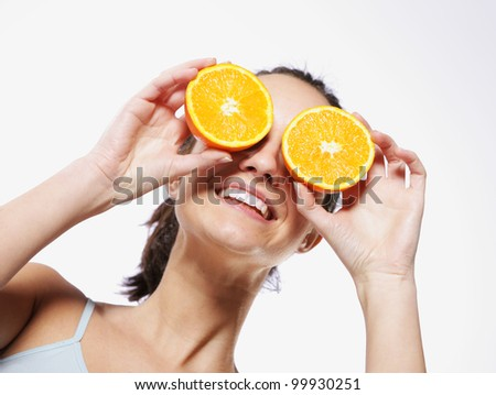 Funny girl portrait, holding oranges over eyes, diet concept - stock photo