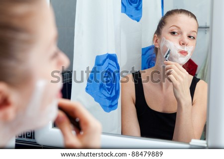 Funny girl shaving her face in bathroom - stock photo