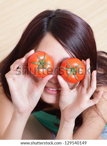 funny girl showing tomato with smile face, cover her eyes, high angle view , asian woman model - stock photo