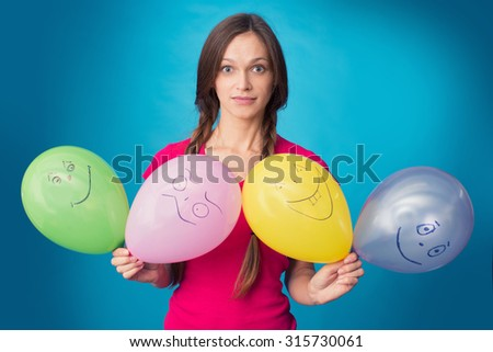 funny girl with balloons over blue background - stock photo