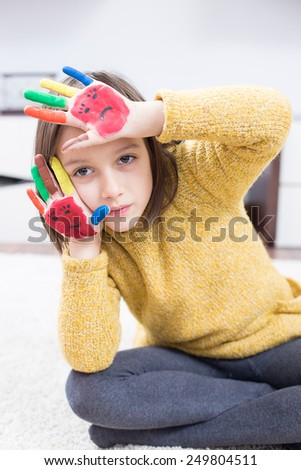 Funny girl with color painted hand - stock photo