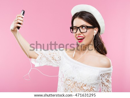 Funny girl with dark hair and red lips wearing white shirt, shorts and glasses posing at pink studio background with mobile phone and smiling.