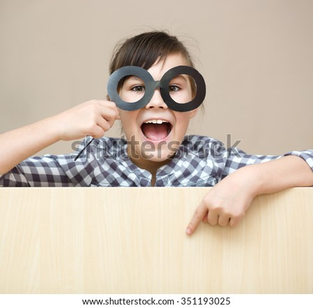 Funny girl with fake glasses. Happy child playing in home - stock photo