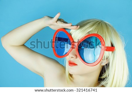 Funny girl with funny glasses, Happy naughty blonde hair woman with giant sunglasses. Woman in crazy clown glasses, Large funny glasses. Looking forward. - stock photo