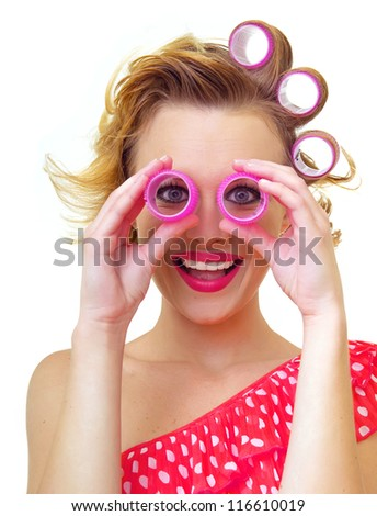 Funny girl with hairstyle looking thro curlers, isolated on white