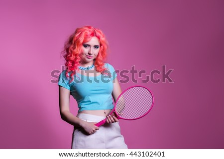 funny girl with pink hair holding racket smiles in the studio , place for text