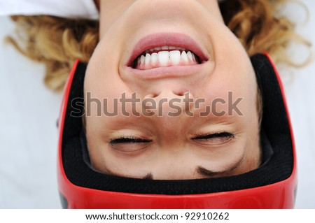 Funny girl with red helmet smiling - stock photo