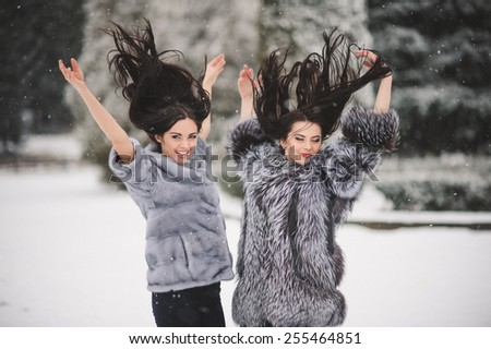 funny girls enjoying winter weather  - with film effect with small grain - stock photo