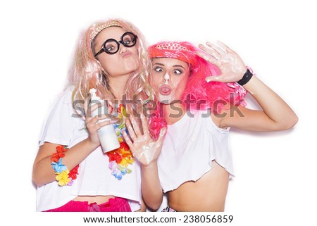 Funny girls in colored wigs and glasses stained with cream play the ape on white background not isolated - stock photo