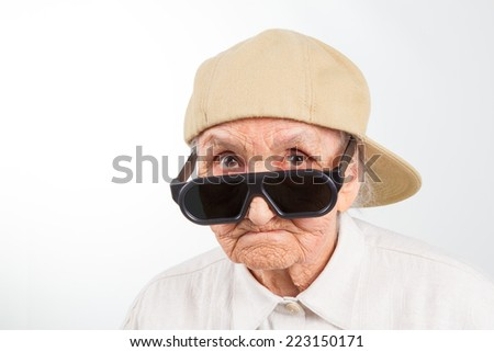 Funny grandma's studio portrait  wearing eyeglasses and baseball cap, isolated on white - stock photo