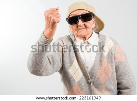 Funny grandma's studio portrait  wearing eyeglasses and baseball cap, who hist with her fist  isolated on white - stock photo
