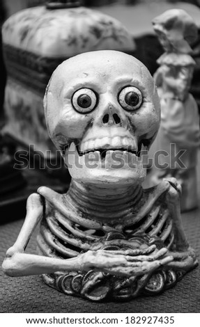 Funny greedy skeleton figurine at flea market in Paris. Aged photo.  Black and white. - stock photo