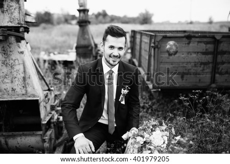 Funny groom is standing among the old equipment