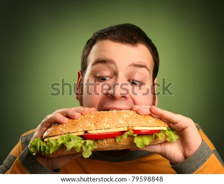 funny guy eating hamburger on green background