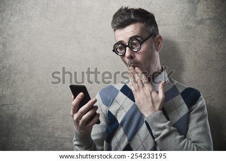 Funny guy having troubles with his smartphone, hand over mouth - stock photo