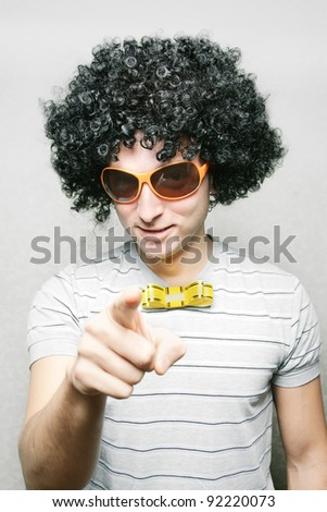 funny guy in afro curly wig with eyeglasses and ribbon bow-tie pointing with his finger - stock photo