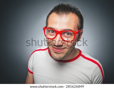 Funny guy looking to you. Close up nerd man over gray background