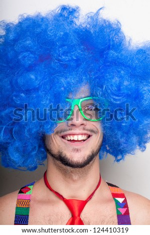Funny guy naked with blue wig and red tie on green background - stock photo