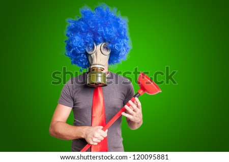 funny guy with gas mak, blue wig and red plunger on green background - stock photo