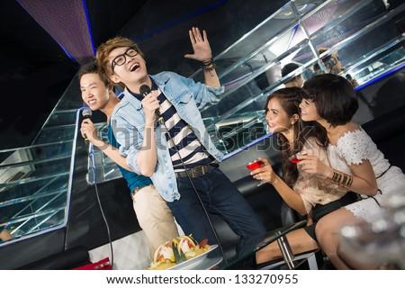 Funny guys singing karaoke to entertain their female friends - stock photo