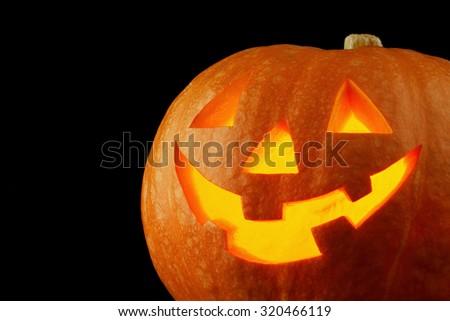 Funny Halloween Jack O' Lantern pumpkin on black background - stock photo