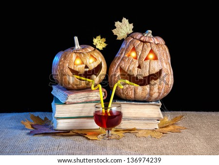 Funny Halloween pumpkins with eyes glowing inside drinking wine on the heap of books at black background - stock photo