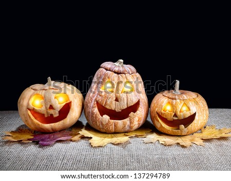 Funny Halloween pumpkins with eyes glowing inside on the dry leaves at black background - stock photo