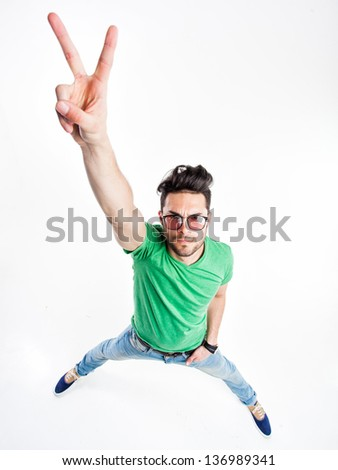 funny handsome man with hipster glasses showing victory and smiling  - wide angle shot - stock photo