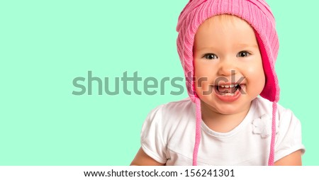 Funny happy baby girl child  in a pink  winter knitted hat laughing - stock photo