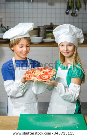 Funny happy chef boy and girl cooking at restaurant kitchen or show pizza - stock photo