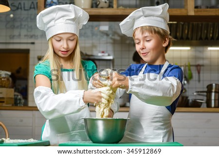 Funny happy chef boy width girl cooking at restaurant kitchen and knead the dough - stock photo