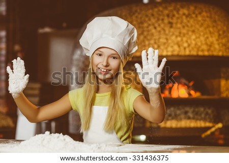 Funny happy chef girl cooking at restaurant kitchen and shows hands in the dough - stock photo
