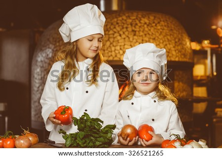 Funny happy chef girls cooking at restaurant kitchen - stock photo