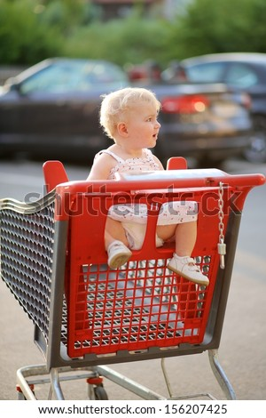 Funny happy little baby girl in beautiful dress sitting in red shopping cart outside of a hypermarket on a parking lot; she enjoys warm summer day, sun is shining at her back - stock photo