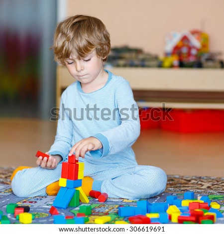 Funny happy  little child playing with lots of colorful wooden blocks indoor. Active kid boy  having fun with building and creating. People, lifestyle, childhood, nursery concept - stock photo