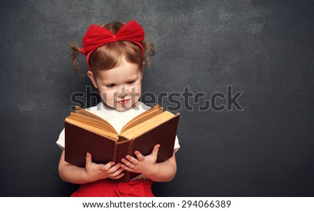 funny happy little girl schoolgirl with a book from the blackboard - stock photo