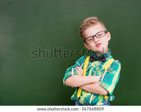 Funny happy nerd near empty green chalkboard - stock photo