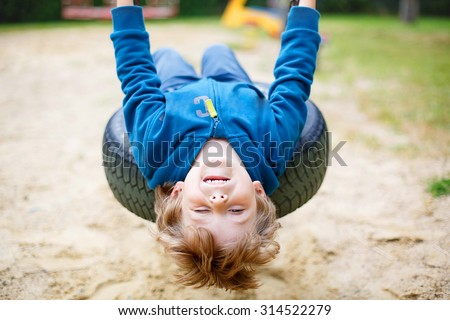 Funny happy preschool kid boy having fun chain swing on outdoor playground. child swinging on warm sunny summer day. Active leisure with kids. Family, lifestyle, summer concept - stock photo