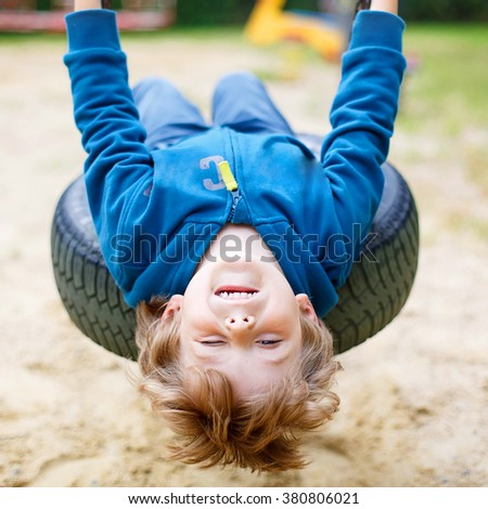 Funny happy preschool kid boy having fun chain swing on outdoor playground. child swinging on warm sunny summer day. Active leisure with kids. Family, lifestyle, summer concept