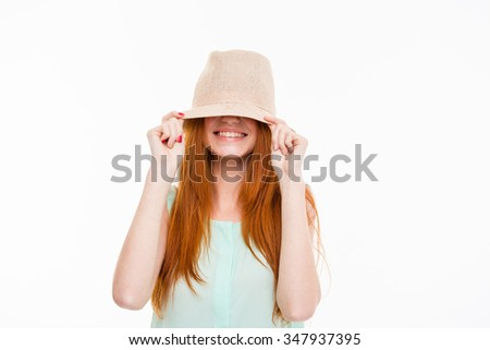 Funny happy smiling amusing young woman with long red hair hiding eyes under boonie hat posing on white background - stock photo