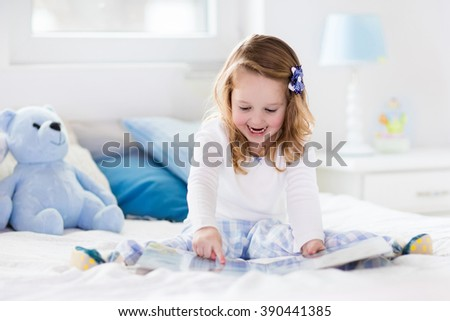 Funny happy toddler girl reading a book and playing with her toy teddy bear in bed. Kids play at home. White nursery. Child in sunny bedroom. Children read and study. Interior for baby and young kid. - stock photo
