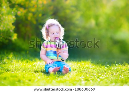 Funny happy toddler girl with curly hair wearing colorful summer shirt and blue jeans sitting on a green lawn eating vanilla and chocolate ice cream cone in a sunny garden - stock photo